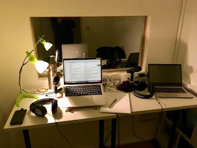 Laptops, Mikros und Kopfhörer auf eienm Tisch vor einer Glasscheibe