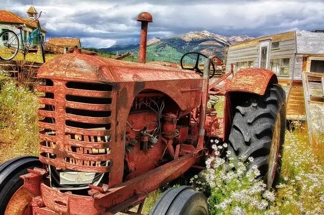 Damaged tractor sitting in a farm yard