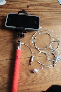 iphone on selfie stick with the  headphones connected. the volume button functions as a remote shutter release.
