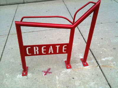 Red metal bike rack shaped like an open book with the word CREATE in open stencil letters