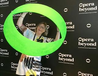 Matleena Laakso poseeraa hymyillen Opera Beyond -hankkeen seinäkkeen edessä.