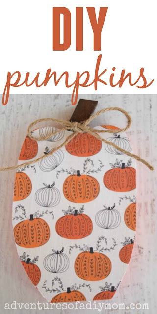painted wooden pumpkin decoupaged with scrapbook paper