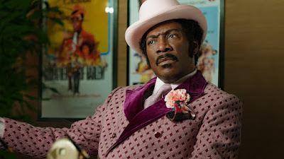 "In ""Dolemite Is My Name,"" Rudy Ray Moore (Eddie Murphy) wears an amazing purple suit to a business meeting about his movie ""Dolemite."""