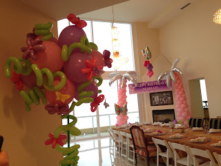 Palm tree balloon columns and flower shaped balloon decor