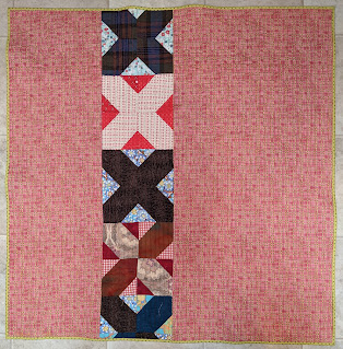 The quilt back includes a row of extra hatchet blocks inserted in a pink plaid