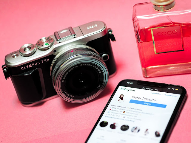 A camera sat next to a mobile phone and bottle of perfume