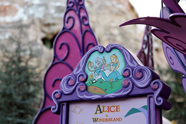 Alice in Wonderland written on board of pink and purple hues