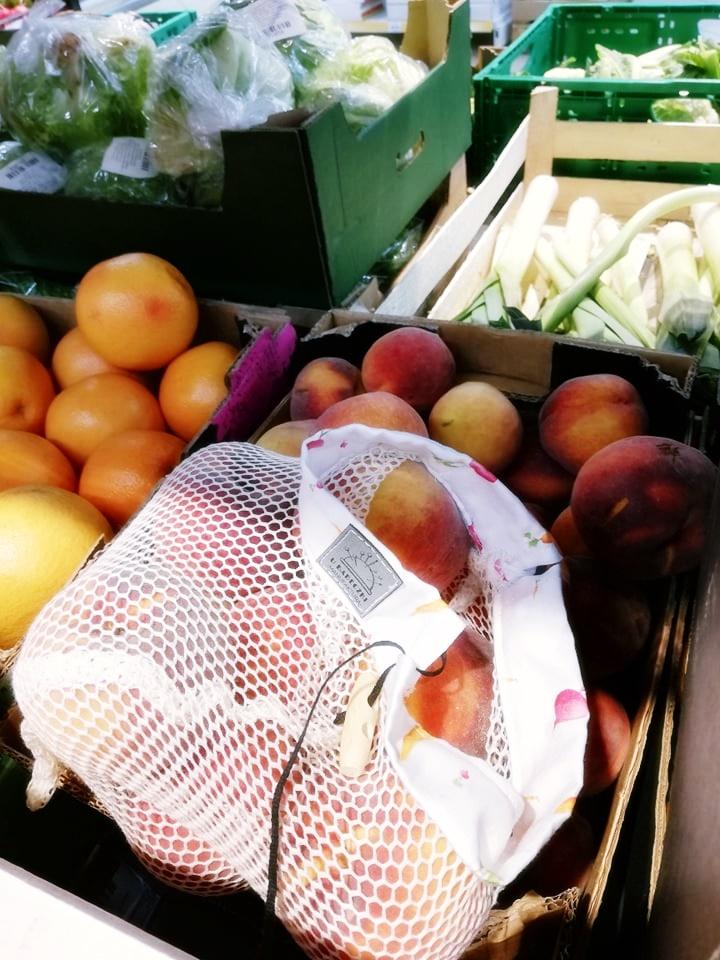 Worek wielorazowy na warzywa i owoce w skrzynce z brzoskwiniami.