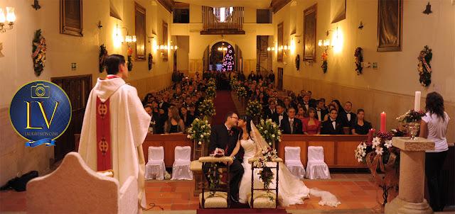Novios sentados se besan delante del sacerdote y todos los invitados