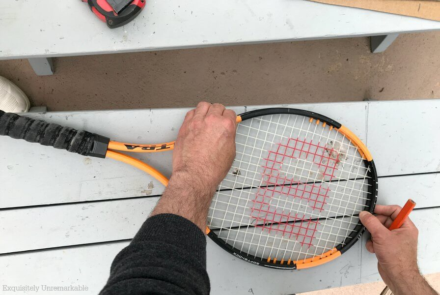 Man drawing a curve on a wooden bench with a tennis racket for pattern