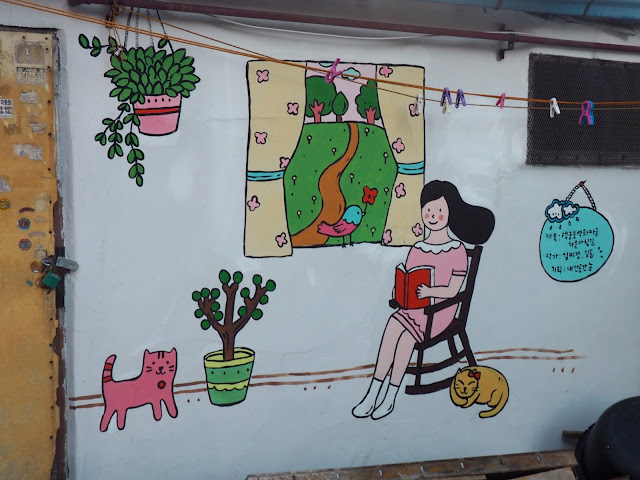 Street art of woman reading with cats in the Haenggung-dong mural village in Suwon, South Korea