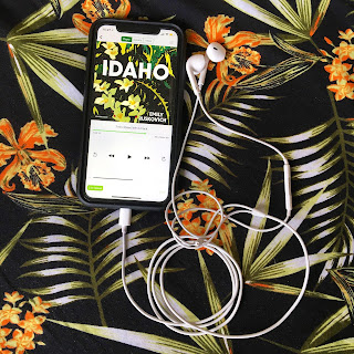 Audiobook of Idaho by Emily Ruskovich on an iPhone with a earphones plugged in, on a floral patterned background