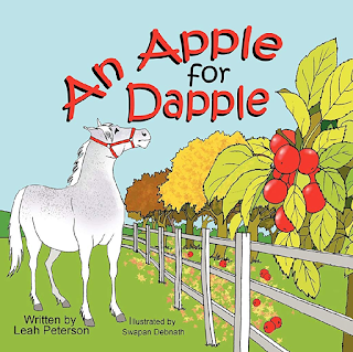 "cover of the book ""An Apple for Dapple"" shows a light gray dappled horse standing in grass next to a white fence and a tree with red apples on it"