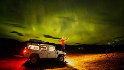 Hombre divisando las auroraas boreales sobre el capó de su coche, una razón para visitar Islandia