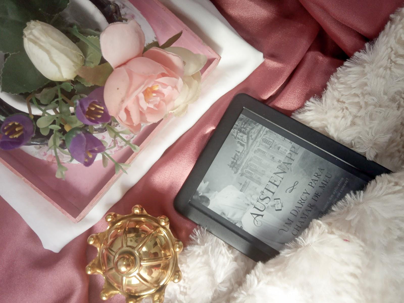 Foto com fundo mesclado vermelho vinho e liso, com uma bandeija em cima de um tecido liso branco contendo um vaso de flores e uma coroa dourada embaixo, no tecido branco e peludo se encontra um kindle com a capa de AustenApp