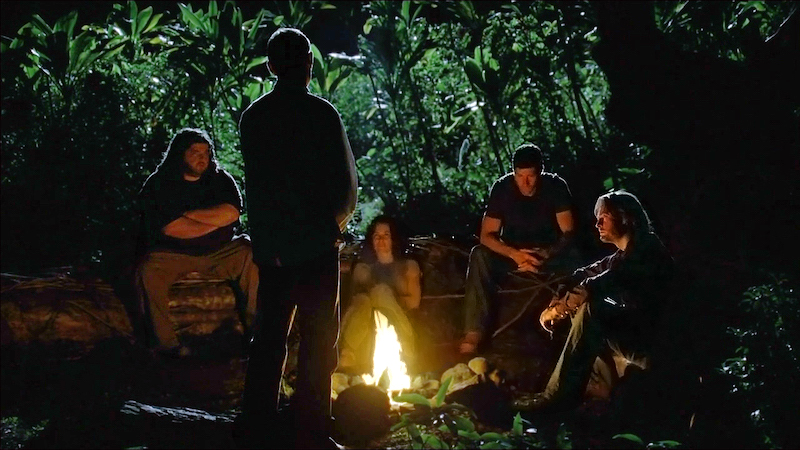 Hurley, Kate, Jack, and Sawyer looking serious around a campfire with shadowed figure of Jacob