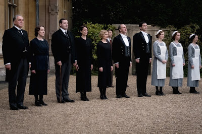 Jim Carter, Phyllis Logan, Brendan Coyle, Raquel Cassidy, Joanne Froggatt, Kevin Doyle, and Michael Fox stand to greet the queen in a movie still for the 2019 drama film Downton Abbey