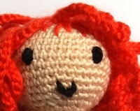 A close up of a doll's smiling face framed by red wavy hair, all crocheted.