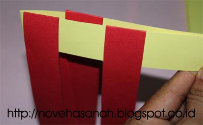 berikutnya kita menambahkan kertas warna merah yang ketiga pada anyaman. lihat betapa mudahnya membuat anyaman dari kertas bekas ini