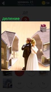 Дом распилен пополам и женщина спиной к мужчине, происходит деление имущества