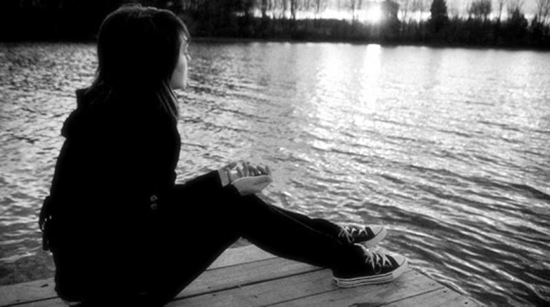 mulher sentada na beira de um pequeno cais contemplando o por do sol a sua frente