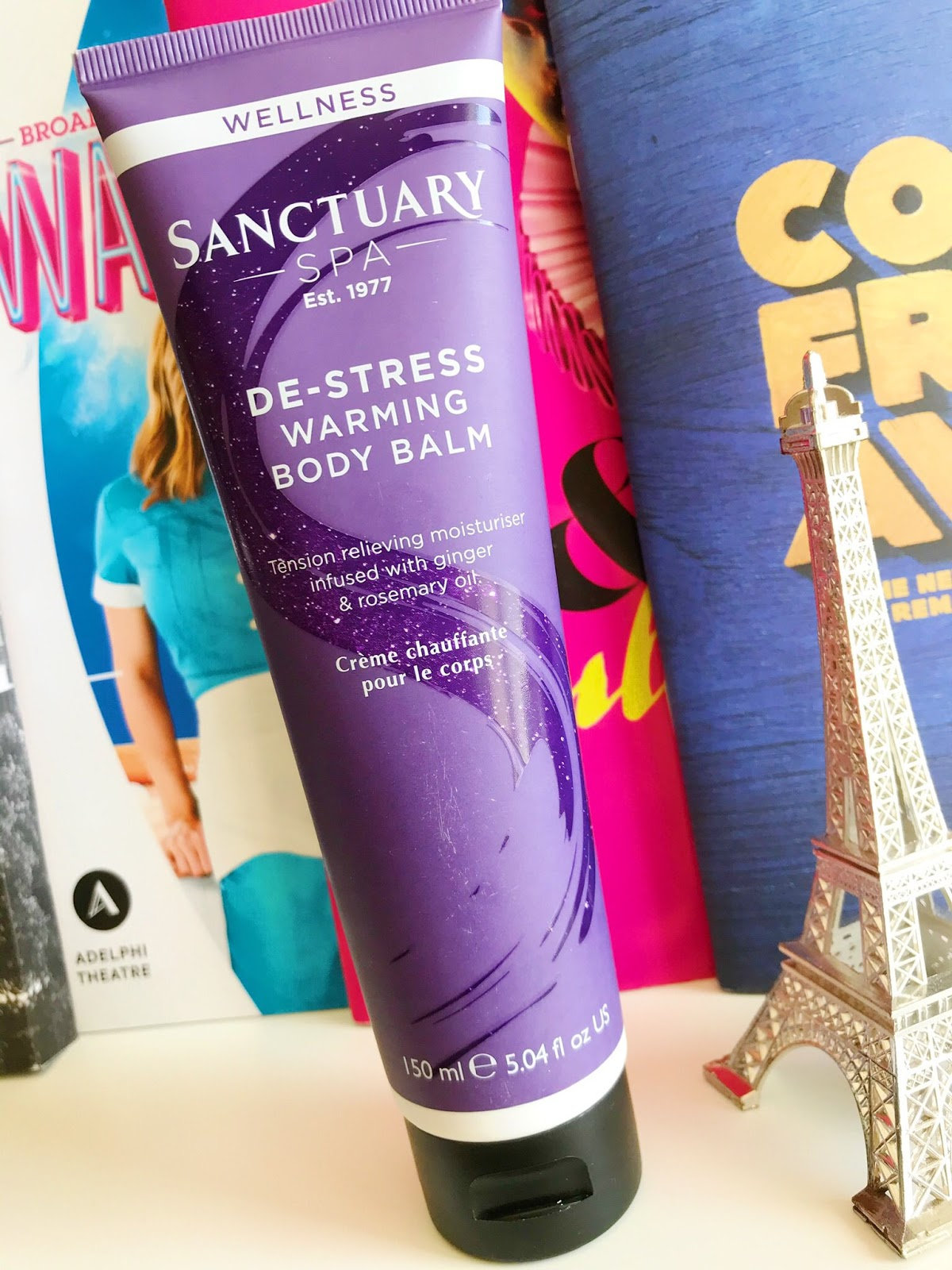 Sanctuary Spa De-Stress Warming Body Balm on desk in front of musical programs