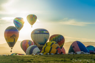 Cramer Imaging's fine art photograph of a hot air balloon cluster taking flight in Panguitch Utah with a sunburst between 2 aerial balloons