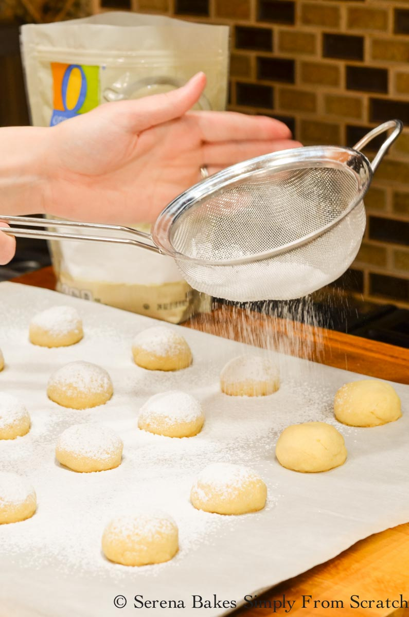 Baked Lemon Snowball Cookies being dusted with powdered sugar.