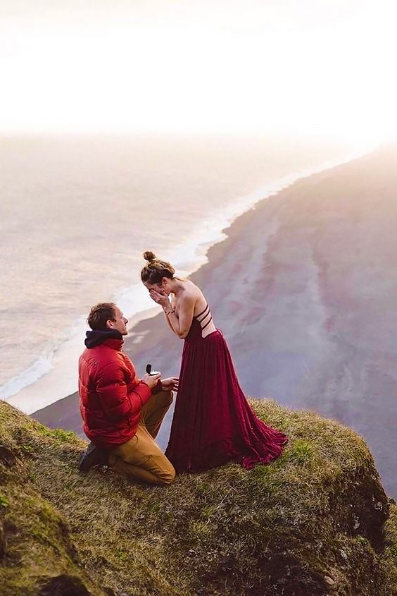 Proposing on a high mountain - Man in red jacket, woman in long maxi
