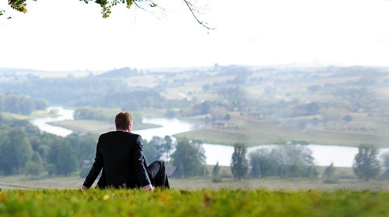 homem sentado na grama contemplando a paisagem à sua frente