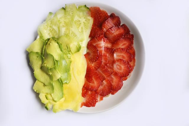 un plato repleto de fruta cortada muy fina, la mitad son fresas y el resto mango, pepino y aguacate