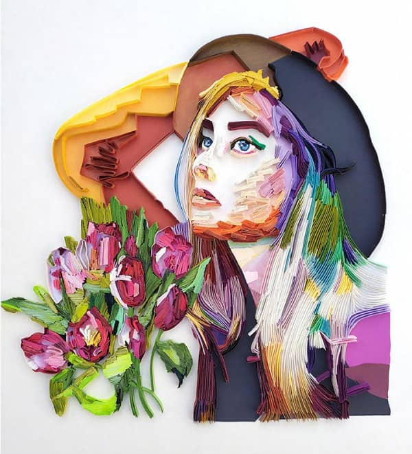 Quilled wall art of woman wearing hat shown with bunch of tulips