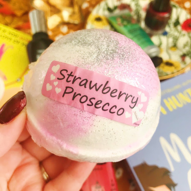 pink strawberry and prosecco bath bomb held up in front of flatlay