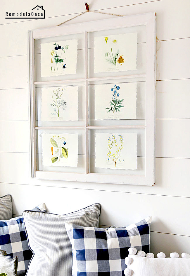 botanical prints adorning an old window as wall art a top a bench with plaid cushions