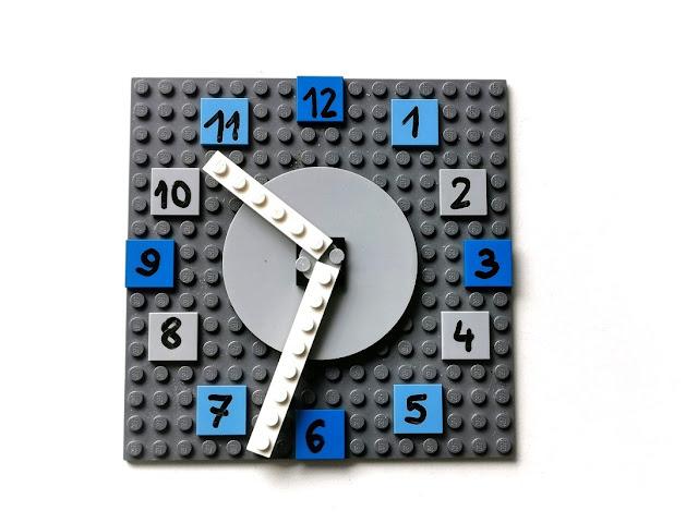 na zdjęciu zegar zbudowany z klocków lego, podstawa to kwadratowa, szara płytka, wokół godziny zapisane mazakiem suchościeralnym