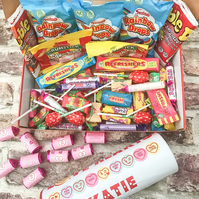Open hamper showing the sweets, with the pink love heart packet and the large tube around the box