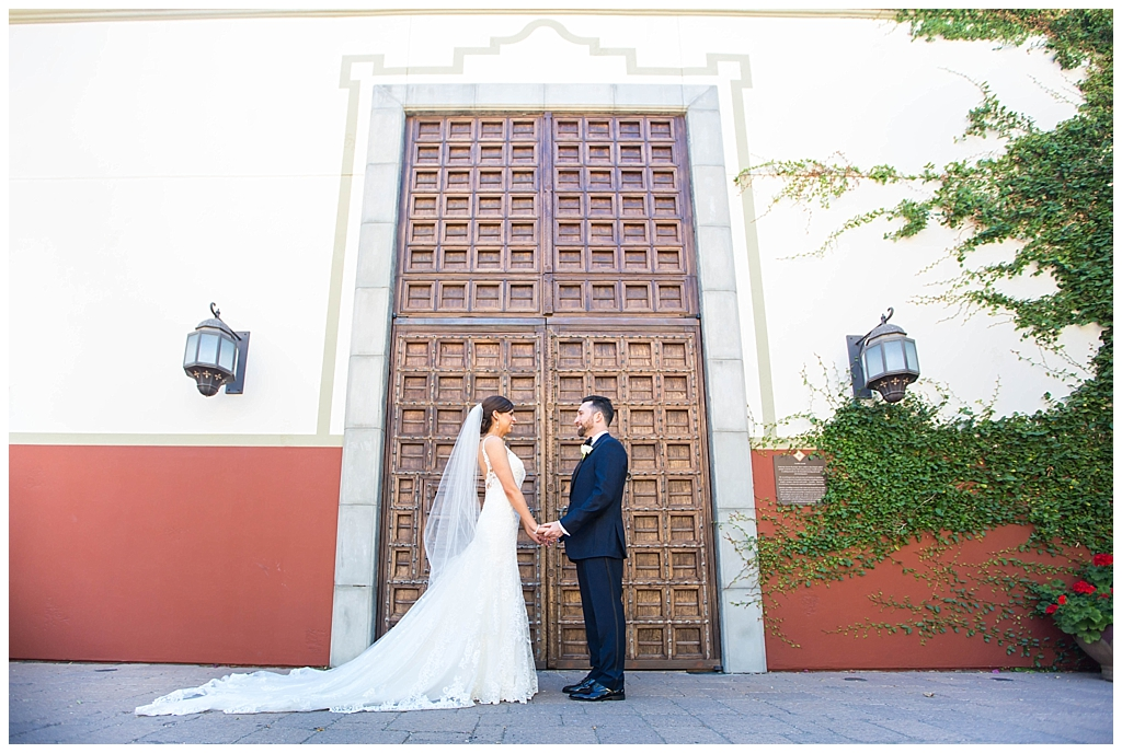 Bride & Groom in front of big wood doors at Omni Montelucia