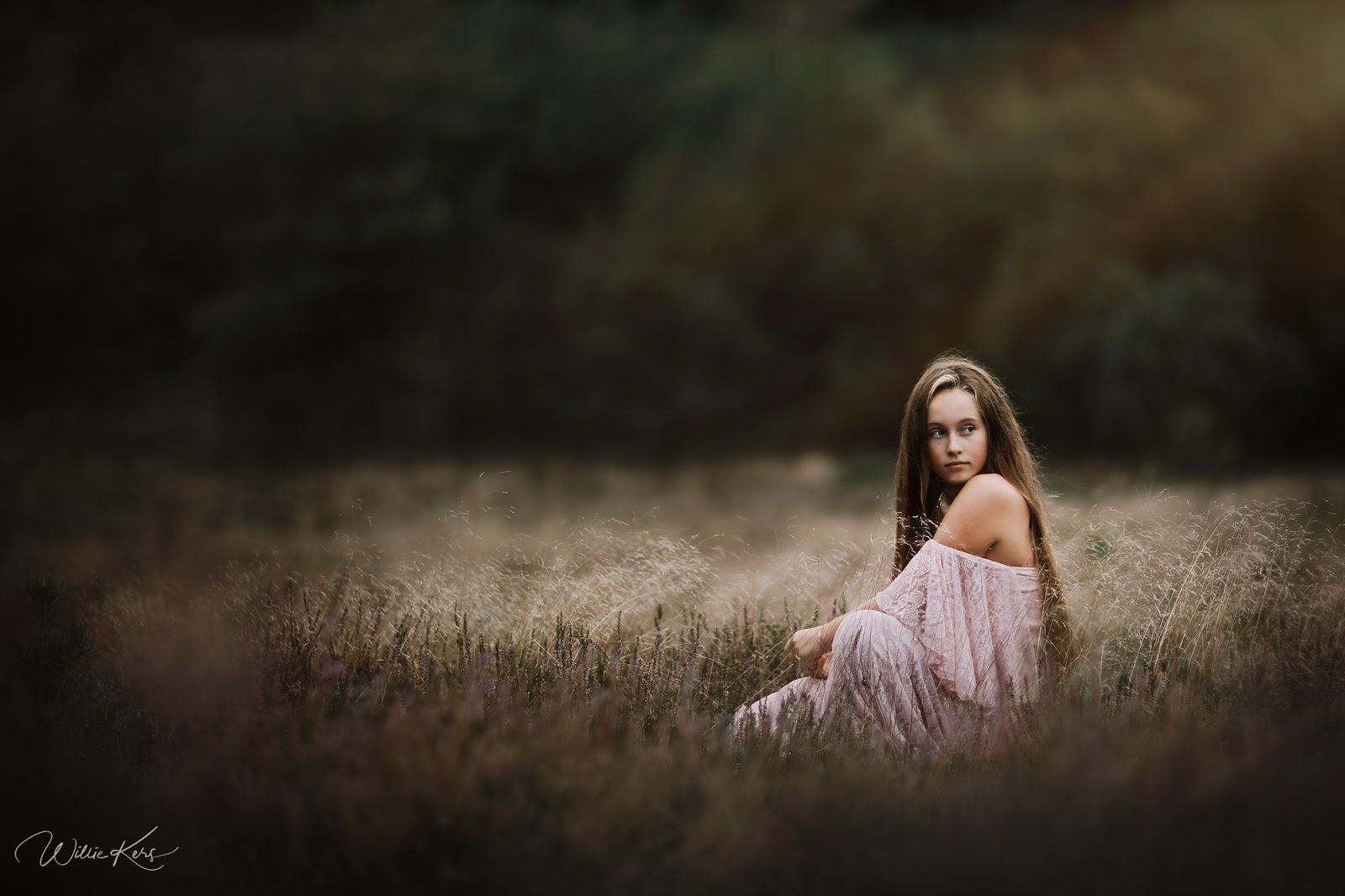 Canon EOS R natuurlijk licht portret van een jonge vrouw of bruid in een trouwjurk zittend in het hoge gras in Apeldoorn door fotograaf Willie Kers