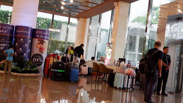 orang-orang membawa koper di lobi hotel grand mercure jakarta