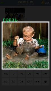 ребенок играет в грязи лопаткой и ведерком