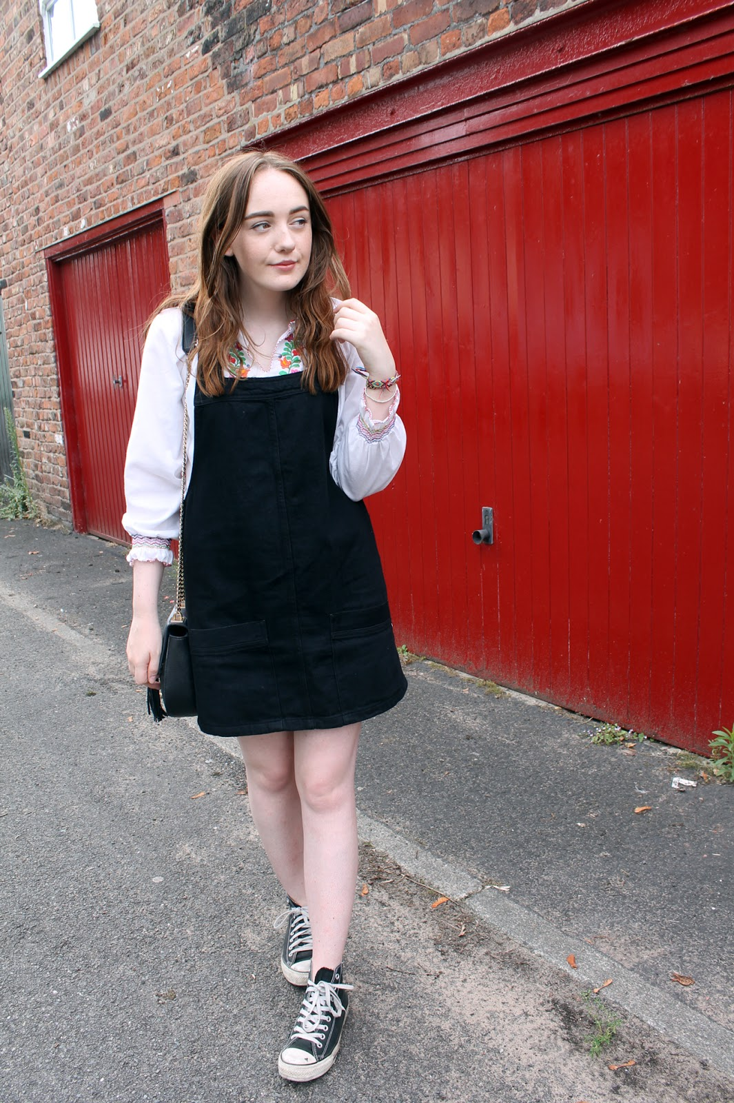 black denim topshop pinafore, white folk style embroidered top, black high top converse