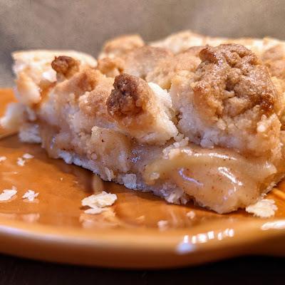 Side view of caramel apple slab pie on orange plate