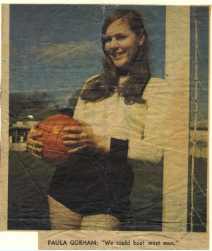 Smiling woman in football kit holding a football and leaning on a goalpost