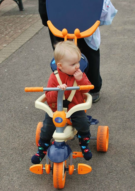Baby on blue and orange trike