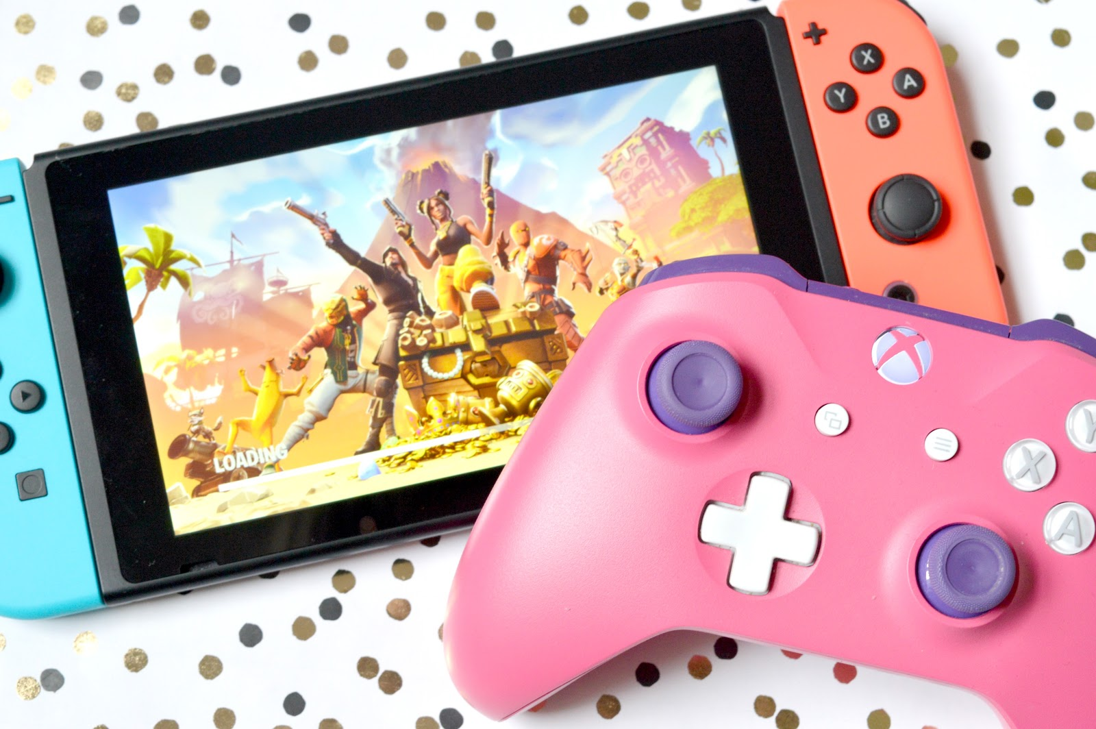 This is a picture of a Nintendo Switch Console with blue and red Joy-Cons and Fortnite loading on the screen. Alongside it is a pink and purple Xbox One controller.