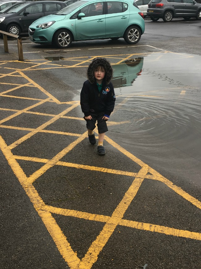 boy-holding-up-his-trouser-legs-standing-near-a-puddle