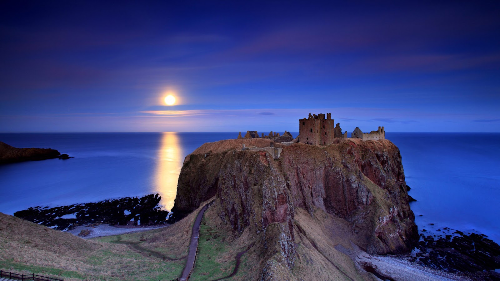 Full moon rising over Dunnottar Castle near Stonehaven on the northeast coast of Scotland