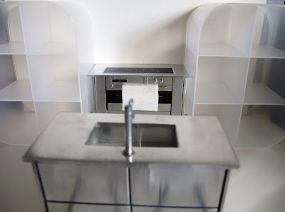Modern dolls' house miniature set up with a metal stove and kitchen unit with sink, and two white perspex shelving unit.