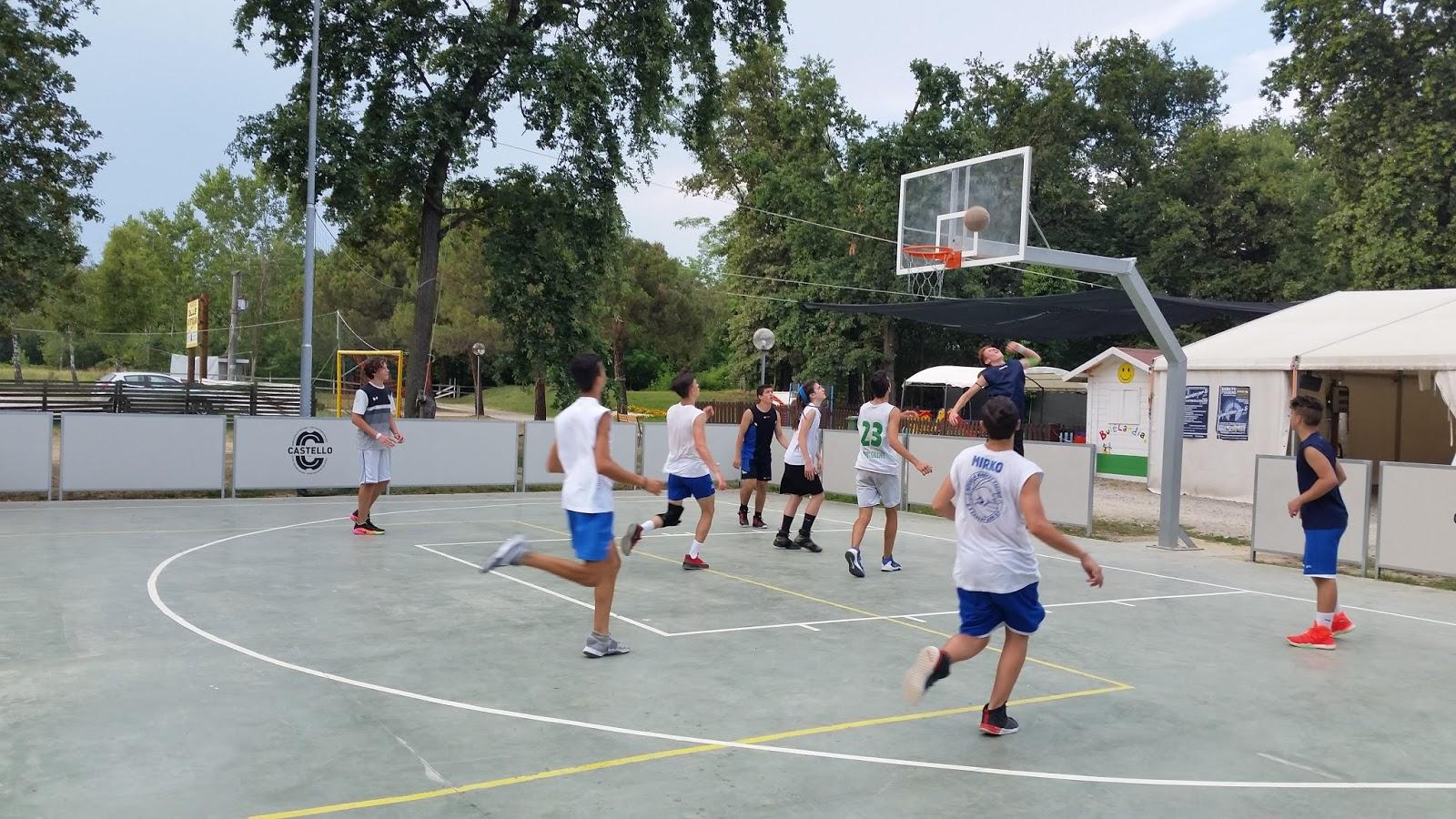 Cestino di pallacanestro sul campo da giuoco al tramonto colorato