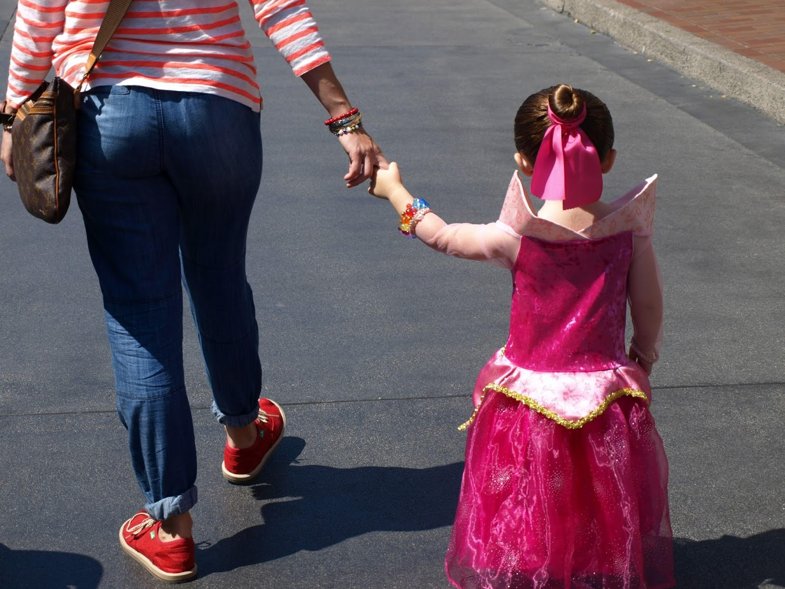 montessori trip family vacation theme park Disneyland. Girl in princess costume holding mother's hand.